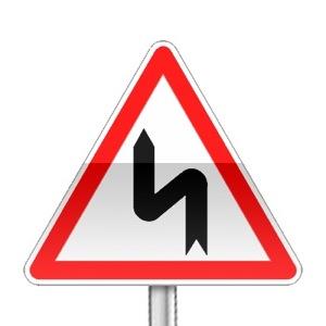 Panneau de danger indiquant une succession de virages dont le premier est à gauche
