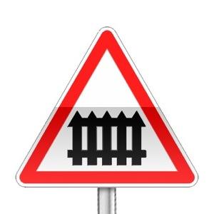 Panneau de danger indiquant un passage à niveau muni de barrières à fonctionnement manuel lors du passage des trains